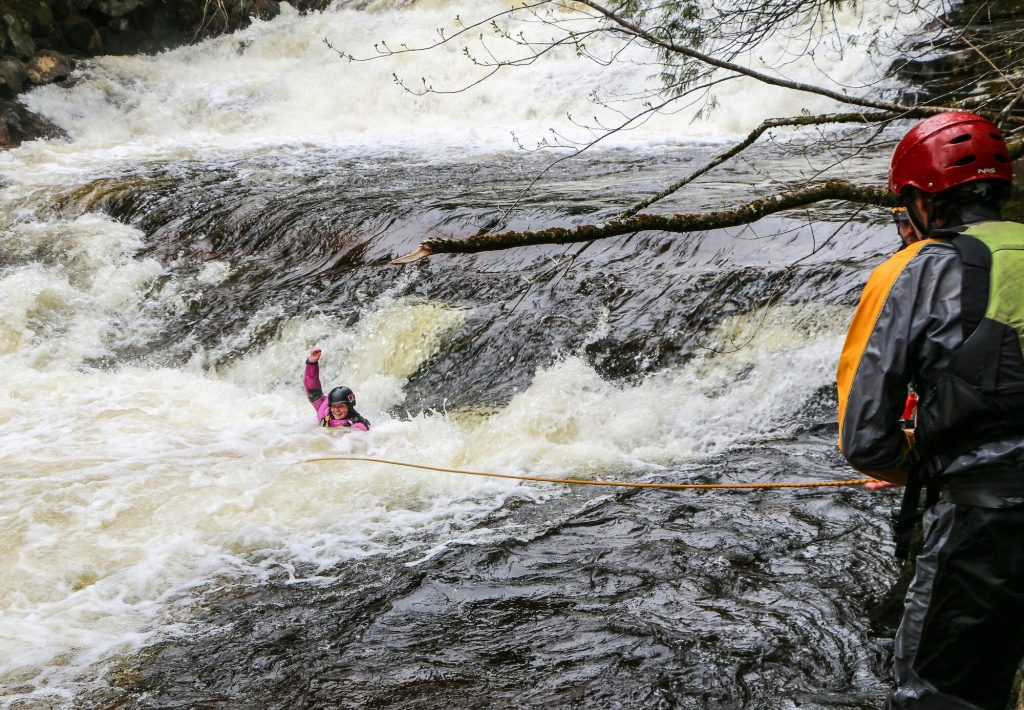 Whitewater rescue throwing rope to swimmer