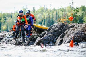 Whitewater rescue paddler using throw bag