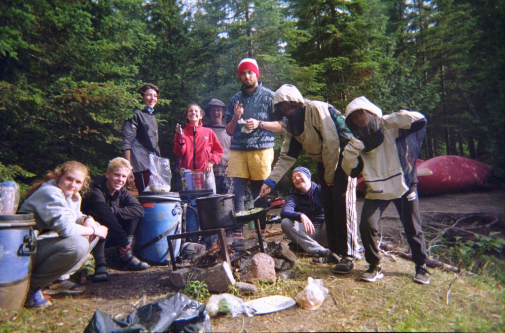 Canoe group sitting around a fire cooking dinner