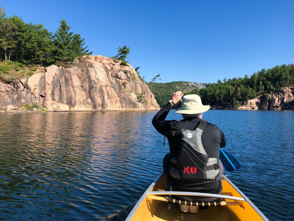 Man paddling a canoe next to red granite rocks in Killarney Provincial Park