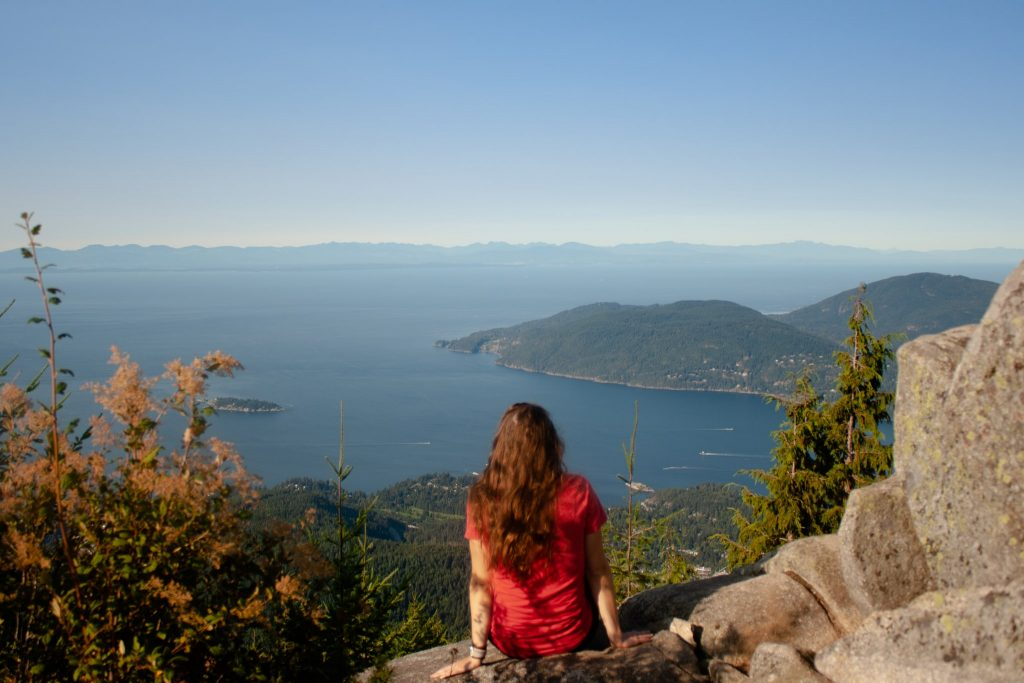 Voyageur Tripper sitting on the edge of a lookout point at Eagle Bluffs in Vancouver. She is wearing a pink t-shirt and women's hiking pants.