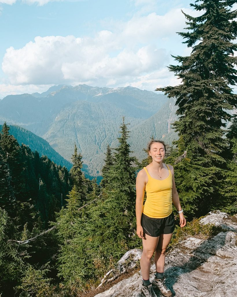 Standing in front of mountains from the top of Mount Fromme hiking trail in Vancouver