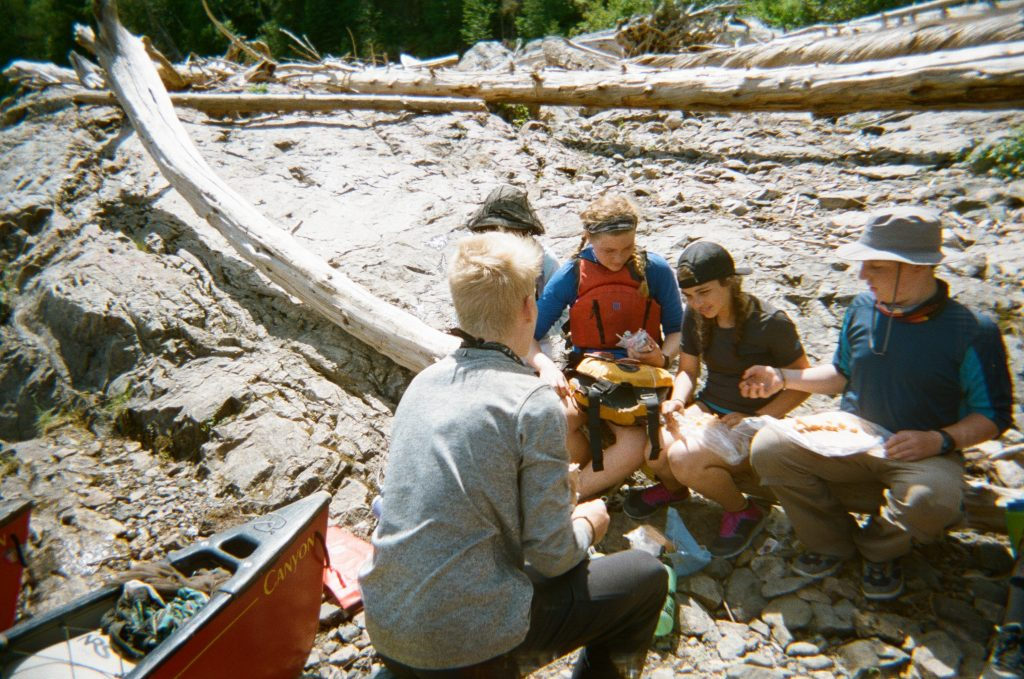 Group of teenagers preparing wraps, a common canoe camping meal, on the shore.