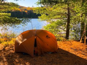 Orange tent next to a river, eco camping in Canada