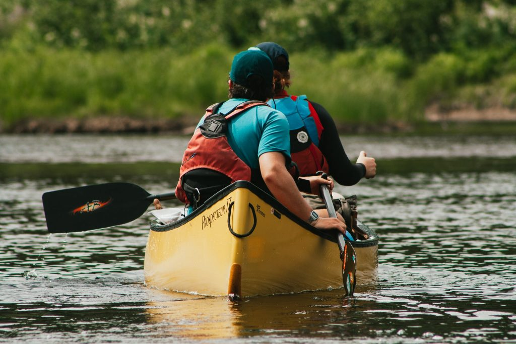 Two paddlers on the Spanish River. wearing Salus and Astral canoeing life jackets