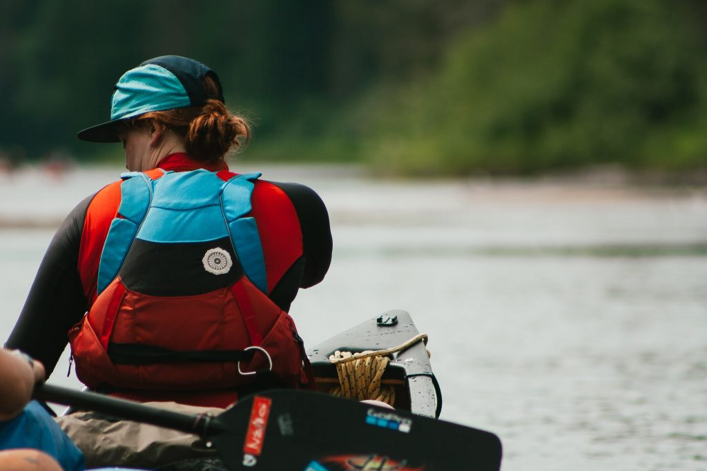 Woman wearing a red and blue canoeing life jackets in a canoe on the Spanish River.