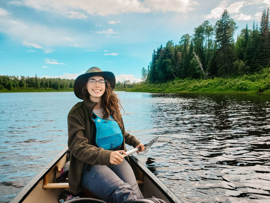 Mikaela paddling on the Missinaibi River. She is holding a black paddle and wearing a wide brimmed hat and a blue life jacket (best canoeing life jacket).
