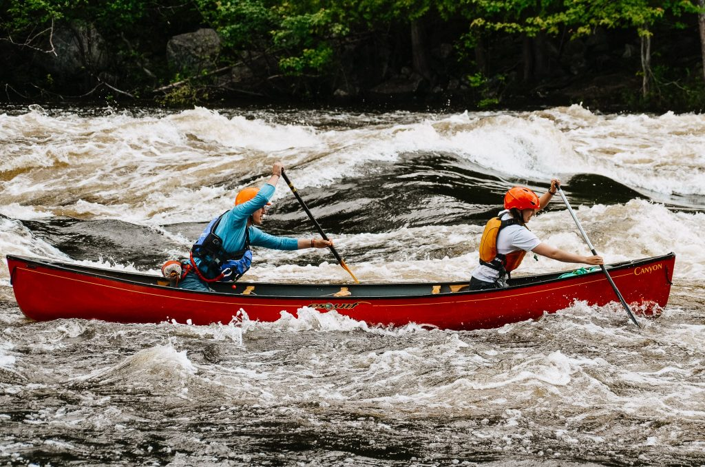 Two paddlers paddling in a red canoe upstream on the Madawaska River.