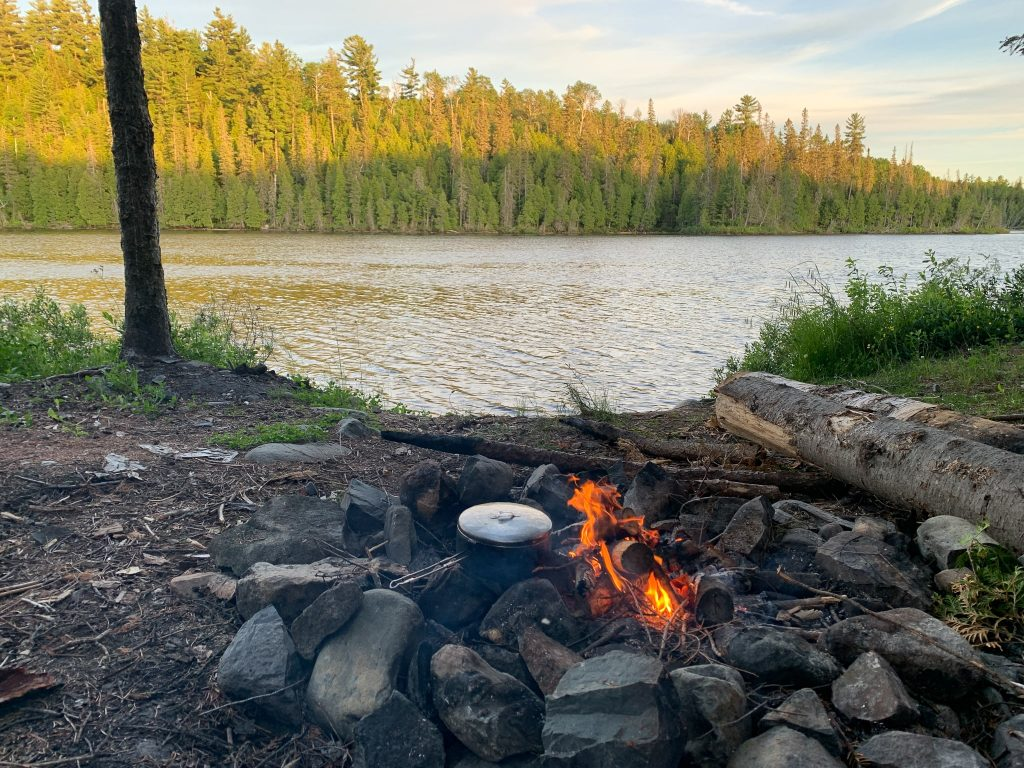 One of my favourite Ontario crown land camping spots. Image shows a pot on a campfire in front of a lake and pine trees.