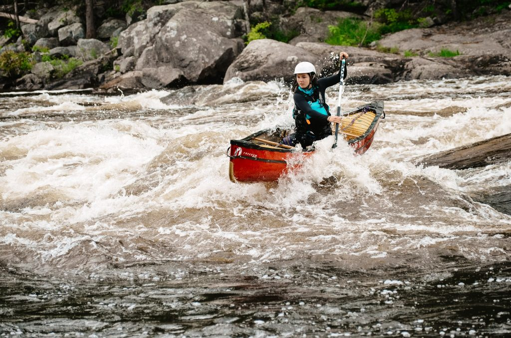 Solo canoeist on the Madawaska River paddling a red canoe.