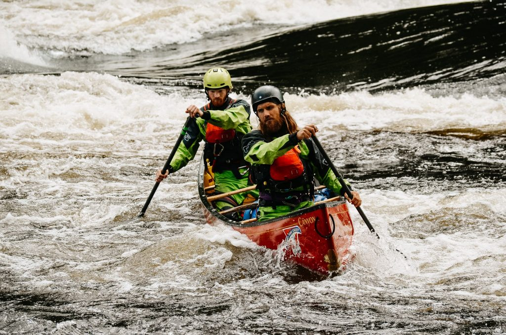 Two paddlers in green drysuits and red paddling life jackets on the Madawaska River.