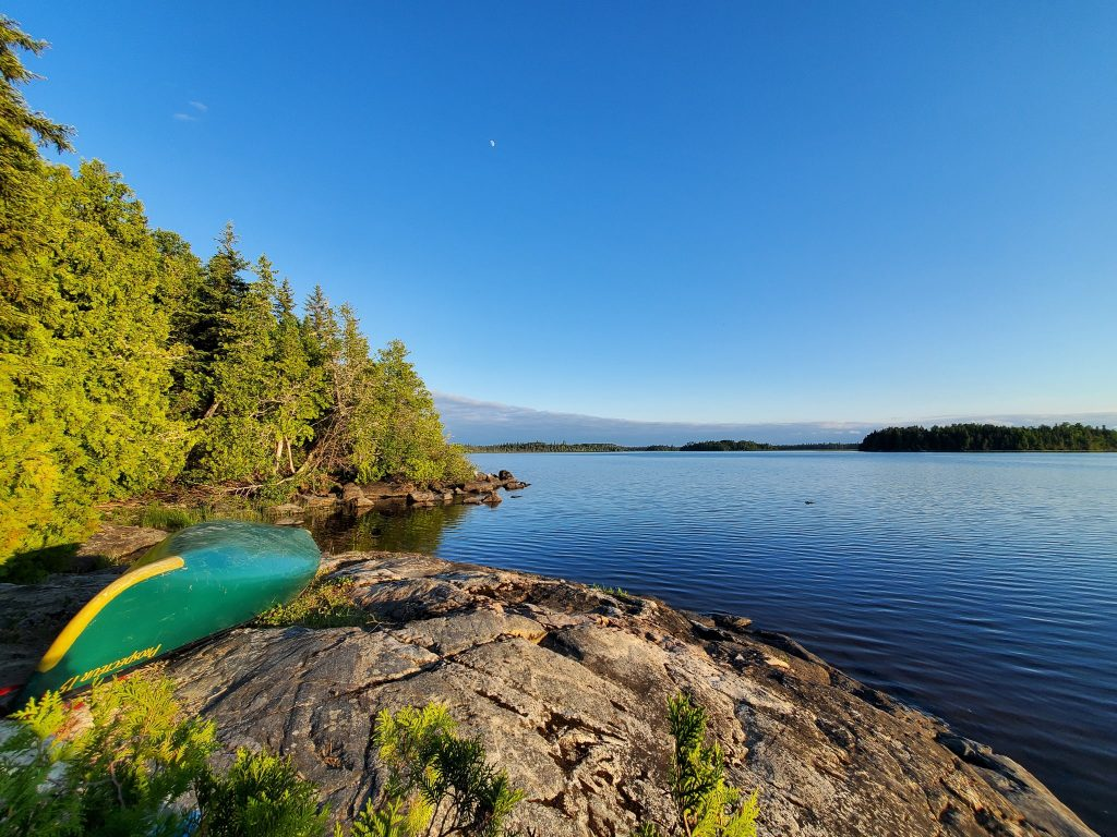 An alternative to Ontario crown land camping is using parks that have backcountry permit systems. Imagine shows green canoe in front of a large lake with pines trees.